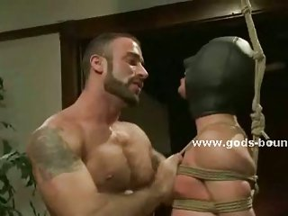 Gagged man has his cock sucked